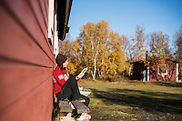 Female hiker relaxes in sun and reads book outside Abiskojaure mountain hut, Kungsleden trail, Lappland, Sweden