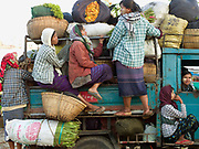 Several women cling on to the sides of a truck loaded with their vegetables and flowers in bamboo baskets and sacks for selling at the local market in Bagan, Central Myanmar, Myanmar (Burma)