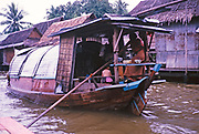 River traffic family houseboat passing wooden houses on waterway near Bankgkok, Thailand in 1964