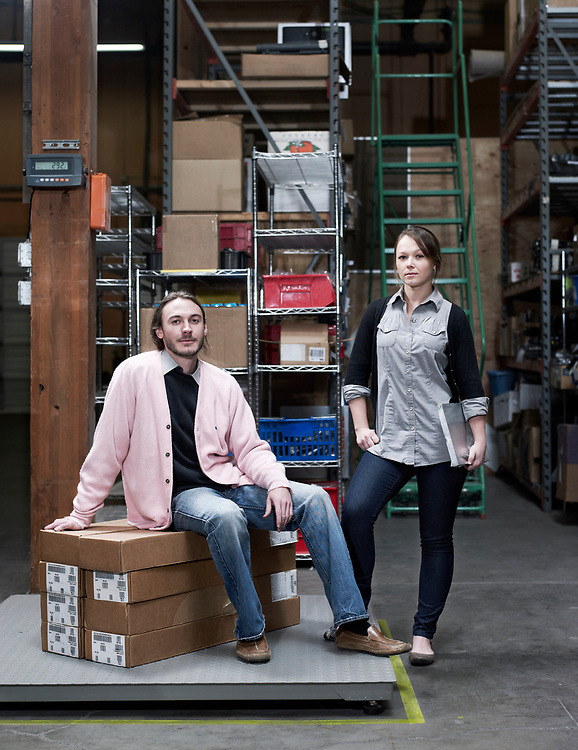 30's something man and woman business owners posing in warehouse