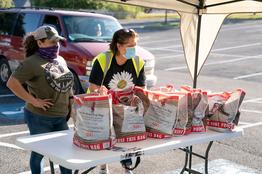Staff members including Arlene Lozano (l) and Anita Swayze help conduct a twice-weekly fresh food drive sponsored by Catholic Charities helping low-income Texans  make ends meet in Austin. The October 1, 2020 effort helped several hundred family members with fruit, meats, milk and cereal.