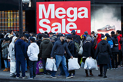 © licensed to London News Pictures. London, UK 26/12/2013. People queueing outside a JD Sports branch on Oxford Street, London on Boxing Day. Photo credit: Tolga Akmen/LNP