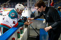 KELOWNA, CANADA - FEBRUARY 15: Devin Steffler #4 of the Kelowna Rockets gets baby powder on his hands by equipment manager Chaydyn Johnson on the bench during warm up against the Vancouver Giants on February 15, 2019 at Prospera Place in Kelowna, British Columbia, Canada.  (Photo by Marissa Baecker/Shoot the Breeze)