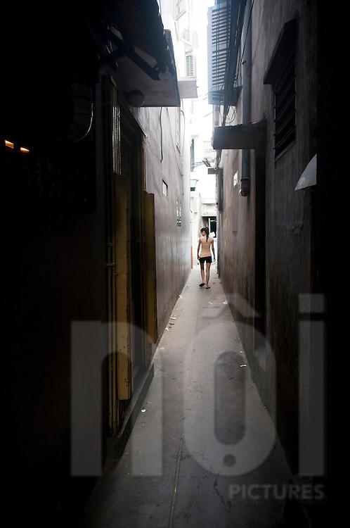 A vietnamese woman walks through a narrow street in Ho Chi Minh, Vietnam, Asia. The corridor gives a noce perspective.