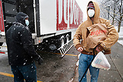 23 NOVEMBER 2020 - DES MOINES, IOWA: People walk away with bags of food during a Thanksgiving food distribution at a park in Des Moines during a snowstorm. The food distribution was organized by Urban Dreams, a community empowerment NGO in central Des Moines, and the NAACP. The food was provided by Hy-Vee, a regional grocery store chain based in Des Moines. They had about 450 meals available. A spokesperson for Hy-Vee said the company was giving away more than 20,000 Thanksgiving meals this year. The Food Bank of Iowa said food insecurity in Des Moines has doubled since the start of the Coronavirus pandemic.   PHOTO BY JACK KURTZ