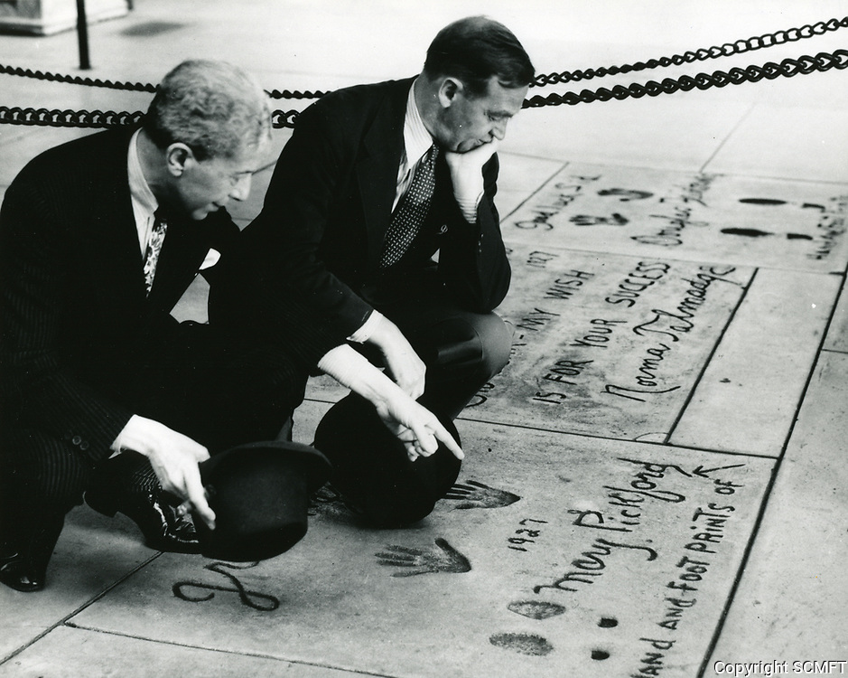 1932 Sid Grauman shows Barry Fitzgerald Mary Pickford's hand and footprint at the Chinese Theater