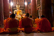 Luang Prabang, Laos. Evening chanting by monks and novices at the Buddhist Temple, Wat Pak Khan.