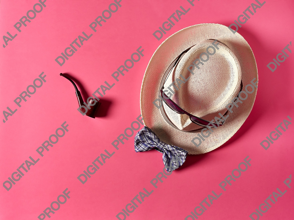 Nice smoking pipe lying on pink background near straw hat with sunglasses and bow tie