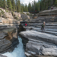 Banff National Park, Alberta, Canada. Photographers frame views of Mistaya Canyon, where the large Mistaya River plunges into a narrow slot canyon it has eroded over time.