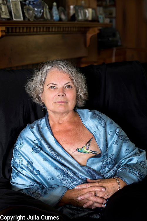 """Darlene Hoyt, 67, is photographed in the home she shares with her husband in West Yarmouth, MA. Darlene was diagnosed with stage one breast cancer four years ago during an annual mammogram.  When more atypical cells were found after two lumpectomies, Darlene underwent a double mastectomy. She recently got a hummingbird tattooed on her left breast area by well-known Cape Cod tattoo artist, Mark Corliss. """"I wore my mastectomy forms for three years. Once I knew I was getting my tattoo, I stopped wearing them. It just felt so false to me. Why pretend to have body parts that I didn't have anymore?  For me, this artwork feels more authentic. I got to change the ending of the story, so to speak,"""" she explains. When the tattoo project is complete, there will be a dragonfly on Darlene's right breast and some words underneath that are meaningful to her. """"I love the tattoo because instead of there being an absence of something, there is an addition of something beautiful,"""" she says."""