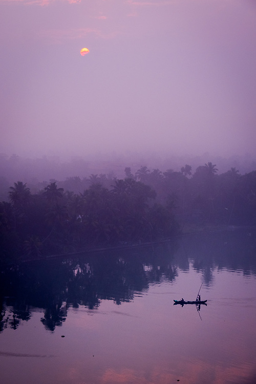 A canoe is crossing at sunrise one of the many rivers that form the backwaters in Kerala, India.
