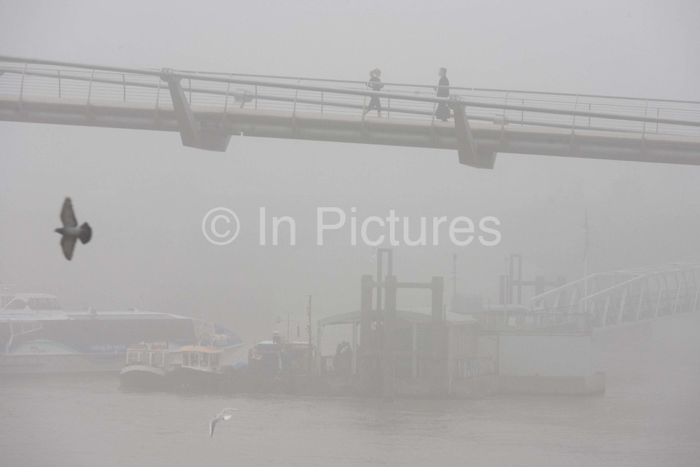 """Morning fog envelopes pedestrians crossing the river Thames on the Millennium Bridge. It is mid-morning but the misty conditions have still to improve enough for visibility to allow a clear view a cross the river where city offices and skyscrapers are normally seen. London's Millennium Footbridge is a steel suspension bridge for pedestrians linking Bankside with the City of London. Construction began in 1998 and it initially opened in June 2000. Londoners nicknamed the bridge the """"Wobbly Bridge"""" after pedestrians initially felt an unexpected swaying motion."""