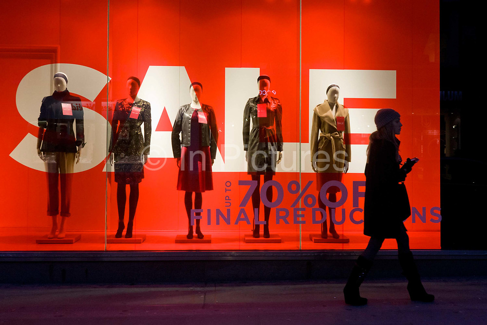 A passer-by walks past a strong design of the front entrance of a retail shop. Giant letters lure potential customers into this branch of Hobbs with a Sale offer sign. Their mannequins are seen in the window of London's Long Acre (street) clothing shop - a line-up of womens' fashion variations displayed in the window on a winter's afternoon. Further reductions are also promised if the potential customer enters the store. With an economic recession taking hold on Britain's high streets and exclusive retail outlets, deals and offers are vital to keep spending and turnover up.