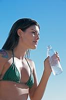 beautiful smiling bikini dressed young brazilian  woman in jericoacoara ceara state near fortaleza drinking water
