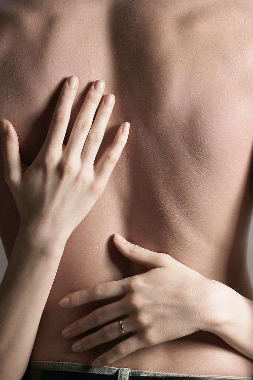 Close up of woman's hands wrapped around back view of man's torso