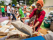 """07 AUGUST 2014 - BANGKOK, THAILAND:       Volunteers stacks sacks of rice before a food distribution program started at Pek Leng Keng Mangkorn Khiew Shrine in Bangkok. Thousands of people lined up for food distribution at the Pek Leng Keng Mangkorn Khiew Shrine in the Khlong Toei section of Bangkok Thursday. Khlong Toei is one of the poorest sections of Bangkok. The seventh month of the Chinese Lunar calendar is called """"Ghost Month"""" during which ghosts and spirits, including those of the deceased ancestors, come out from the lower realm. It is common for Chinese people to make merit during the month by burning """"hell money"""" and presenting food to the ghosts. At Chinese temples in Thailand, it is also customary to give food to the poorer people in the community.  PHOTO BY JACK KURTZ"""