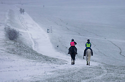 © Licensed to London News Pictures. 12/04/2021. Epsom, UK. Horses exercise as snow hits Epsom Racecourse in Surrey. Unusually late spring snow is hitting parts of teh UK today as lockdown restrictions are being eased today.  Photo credit: Peter Macdiarmid/LNP