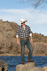 cowboy standing on a river rock