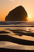 The setting sun shines through the arch of Haystack Rock, located off Cape Kiwanda on the Oregon Coast near Pacific City, Oregon.