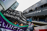 Here, passing a luxury Barratt development at Aldgate. People marched from South London and East London to City Hall to demand better homes for Londoners and an end to the housing crisis. Demands included rent controls, affordable and secure homes for all, an end to the Bedroom Tax and welfare caps and the building of new council houses. The event was called by Defend Council Housing and  South London People's Assembly. And the East London route started at Parish Church of St. Leonard, Shoreditch, London, United Kingdom. 31 Jan 2015.