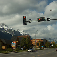 Cars traverse a street in Canmore, Alberta, below Mount Rundle in Banff National Park.