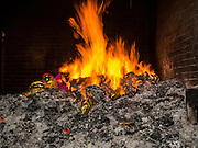 """06 AUGUST 2014 - BANGKOK, THAILAND:  Hell money is burned at Wat Mangkon Kamalawat, a large Chinese Mahayana Buddhist temple in Bangkok. Burning """"hell money"""" is common during Hungry Ghost month.   PHOTO BY JACK KURTZ"""