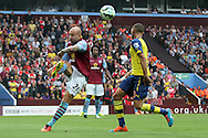 Alan Hutton of Aston Villa clears the ball under pressure from Kieran Gibbs of Arsenal. Barclays Premier league match, Aston Villa v Arsenal at Villa Park in Birmingham on Saturday 20th Sept 2014<br /> pic by Mark Hawkins, Andrew Orchard sports photography.