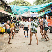 Burmese men playing chinlone (caneball) on a street in Mandalay, Myanmar (Burma).