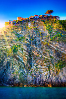 """""""Corniglia courtyard peak on the Tyrrhenian sea""""...<br /> <br /> I began my daily journey at the northern most town of Monterosso and took the train to the southernmost town of Riomaggiore. I sailed up the coast photographing each Cinque Terre town along the way aboard the Angelina Dada. Upon arriving back home in Monterosso, soft light illuminated the sky and azure sea of the Mediterranean convincing me to sail all the way back to Riomaggiore with my gracious guides Claudio and Eddie of """"Cinque Terre dal Mare"""" sailing excursions. We arrived just in time for a perfect sunset. After a nice dinner...I caught the last train at midnight back home to Monterosso. A very long day, but worth every minute!  This image of Corniglia, the only Cinque Terre town not directly on the sea…was taken at the beginning of the journey from Riomaggiore. <br /> The colorful village dwellings  seemed to desperately hang high atop the dramatic cliff top as the evening sun graciously kept us warm."""