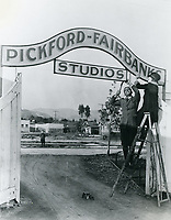 1922 Mary Pickford & Douglas Fairbanks pose for a publicity photo at the entrance to their new studio on Santa Monica Blvd. (in the background). This sign was never permanently hung above the entrance gates.