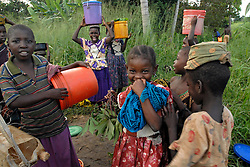 Village children collect water near sunset in the village of Simana, leaving them extremely vulnerable to lion attacks who catch them in the thick grass. Ami vitale