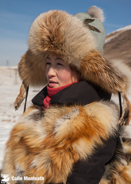Woman in fox fur hat, Kazakh eagle hunters from far western province of Bayan Olgii compete in winter festival, Mongolia.
