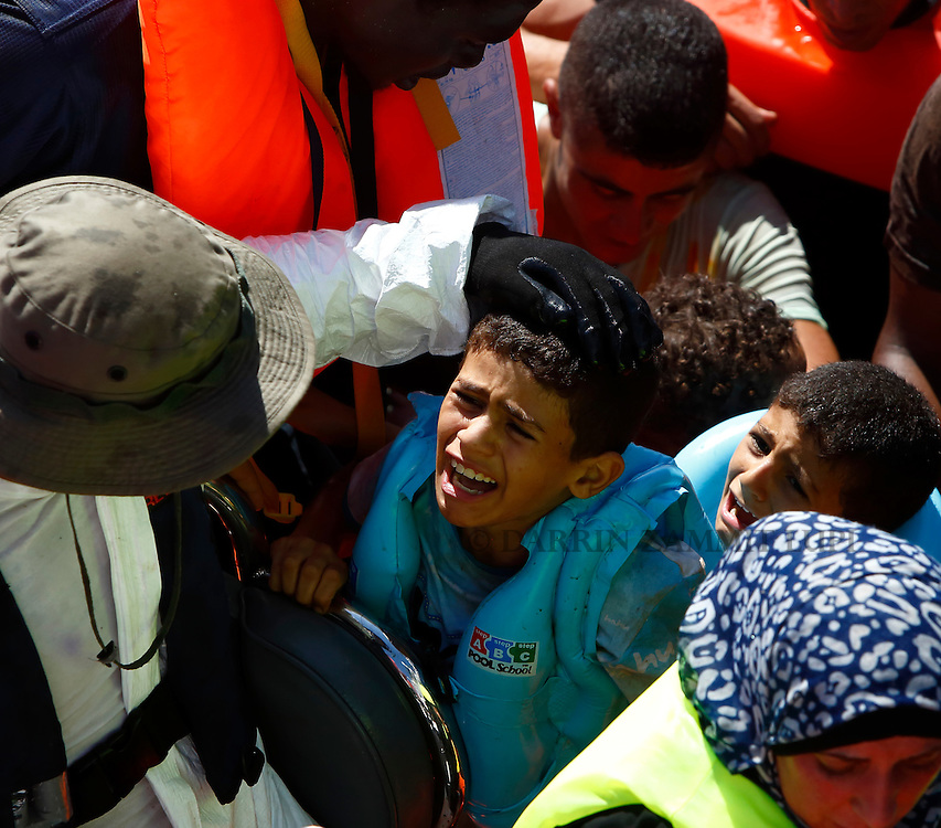 Migrant children cry as they arrive alongside the Migrant Offshore Aid Station (MOAS) ship MV Phoenix after being rescued from an overloaded wooden boat off the coast of Libya August 6, 2015.  An estimated 600 migrants on the boat were rescued by the international non-governmental organisations Medecins san Frontiere (MSF) and MOAS without loss of life on Thursday afternoon, a day after more than 200 migrants are feared to have drowned in the latest Mediterranean boat tragedy after rescuers saved over 370 people from a capsized boat thought to be carrying 600.<br /> REUTERS/Darrin Zammit Lupi <br /> MALTA OUT. NO COMMERCIAL OR EDITORIAL SALES IN MALTA