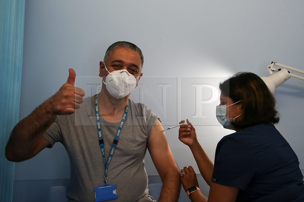 © Licensed to London News Pictures. 17/09/2021. London, UK. Balvinder Kullar gestures as Dr Sheena Patel administers the booster Covid-19 vaccine at a vaccination centre in north London. The coronavirus vaccine booster campaign begins in England with frontline NHS and social care staff, people aged 50 and over, and those aged 16 and over with health conditions are eligible for a full dose of the Pfizer vaccine, or a half-dose of Moderna vaccine. Photo credit: Dinendra Haria/LNP