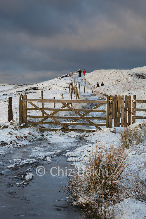 Scenic winter view with gate, snow and ice looking along the track from Cat & Fiddle to Errwood (and Shining Tor) on a cold winter's late afternoon, Peak District National Park