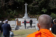 A Buddhist Monk watches Canadian Ambassador,  Ian Burney and a Canadian military officer lay a wreath of poppies at the Cross of Sacrific during the Remembrance Sunday ceremony at the Hodogaya, Commonwealth War Graves Cemetery in Hodogaya, Yokohama, Kanagawa, Japan. Sunday November 12th 2017. The Hodagaya Cemetery holds the remains of more than 1500 servicemen and women, from the Commonwealth but also from Holland and the United States, who died as prisoners of war or during the Allied occupation of Japan. Each year officials from the British and Commonwealth embassies, the British Legion and the British Chamber of Commerce honour the dead at a ceremony in this beautiful cemetery.