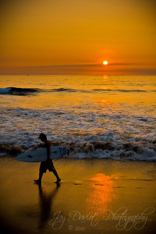 A surfer walking the beach at sunset in Montanita, Ecuador.