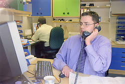 Man with disability; who is wheelchair user; working at computer in office talking on telephone,