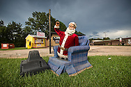 Santa Clause in an oversized chair with a broken TV in front of a business that flooded in Baton Rouge dudring the 1000 year flood.