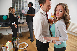 Woman rejecting unwanted advances from man at party.