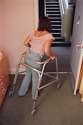 Teenage girl with physical disability walking with assistance of metal frame,