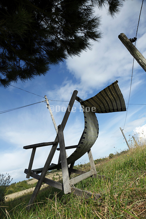 reclining wooden folding chair under a tree