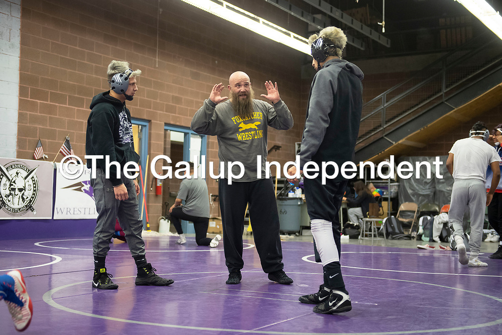 Miyamura wrestling coach Nate Sellers, center, talks with Drake Guerrero, left, returning state champion and  <br /> Sean Matthew Garcia, district champion, Tuesday afternoon during practice at Miyamura High School. Miyamura High School is sending 12 boys and 7 girls to compete at the New Mexico Athletic Association state wrestling tournament this weekend at the Santa Ana Star Center in Rio Rancho.