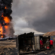 En quittant la région de Qayyarah (Nord de l'Irak) en août 2016, les troupes de Daesh ont incendié 25 puits de pétrole. Depuis, les pompiers irakiens travaillent tous les jours pour éteindre ces gigantesques feux qui émettent d'épaisses colonnes de fumée noire et toxique. Irak, Qayarrah, 6 février 2017.<br /> Leaving the Qayyarah region (Northern Iraq) in August 2016, Daesh's troops set fire to 25 oil wells. Since then, Iraqi firefighters have been working daily to extinguish these gigantic fires that emit thick columns of black and toxic smoke. Iraq, Qayarrah, February the 6th 2017.