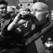 Piper band plays ahead fo the annual Highland Games, 3rd of August 2019, Newtonmore, Scotland, United Kingdom. Pipers have a drink from a hip flask ona small break in playing. The band is a mix of various bands from around the highlands. They meet in the centre of Newtonmore and march through the town and out to the playing fields where the games are held. The day is hot and many of the pipers are struggling in the heat. The Highland Games is a traditional annual event where competitors compete as strong men, runners, dancers, pipers and at tug-of-war. The games go back centuries and are happening through-out the summer across Scotland. The games are both an important event locally and a global tourist attraction.