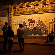 December 08, 2012 - Cairo, Egypt: Bystanders look at a satirical graffiti outside the presidential Palace in central Cairo...Sporadic clashes between supporters and opponents of president Mohamed Morsi, erupted in the past week over his assumption of extraordinary powers and the scheduling of a referendum on a disputed draft of the new constitution...Thousands of opposition protesters rallied outside the palace, in Cairo's Tahrir Square, and in cities and towns across the country, calling for an end to Mr Morsi's power grab and the shelving of the draft constitution. (Paulo Nunes dos Santos/Polaris)