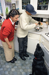 Single mother watching teenage son prepare dinner for the dog in kitchen,
