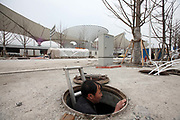 A man climbs out of a man hole in front of the glass funnel-like structure of Sun Valley at the 2010 Expo site in Shanghai, China on 22 January 2010. Shanghai eventually spent some 40 billion usd in developing the expo site and related infrastructure, and saw a record breaking 70 million visitors, the site has seen limited use after the end of the expo.