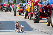 A child picks up candy from the street during the Independence Day parade in Millville, Pennsylvania on July 5, 2021.