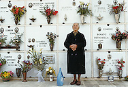 A woman in Italy standing in front of her husband's grave, in front of the space her body will one day occupy.